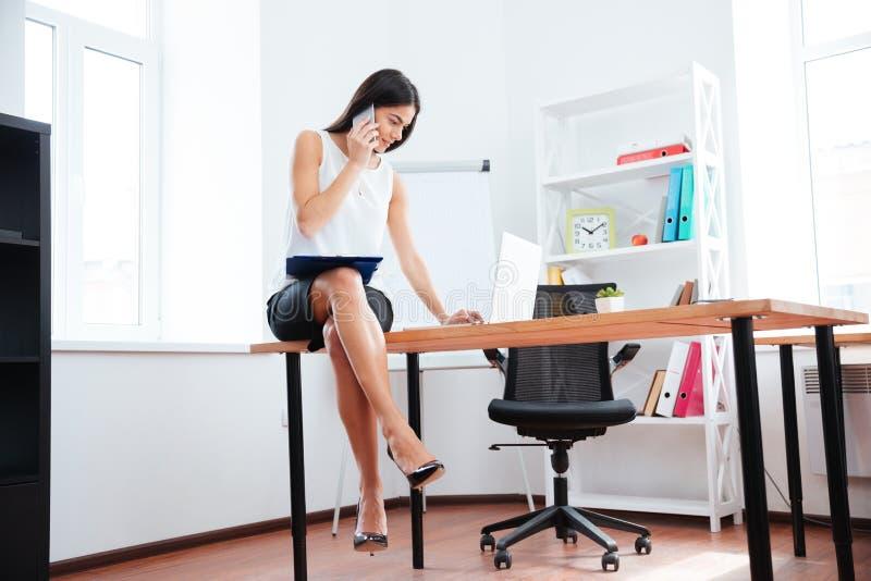 Επιχειρηματίας που λειτουργούν με το τηλέφωνο και φορητός προσωπικός υπολογιστής στην αρχή στοκ εικόνες