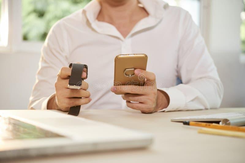 Επιχειρηματίας που ελέγχει το χρόνο στις συσκευές του στοκ εικόνες με δικαίωμα ελεύθερης χρήσης
