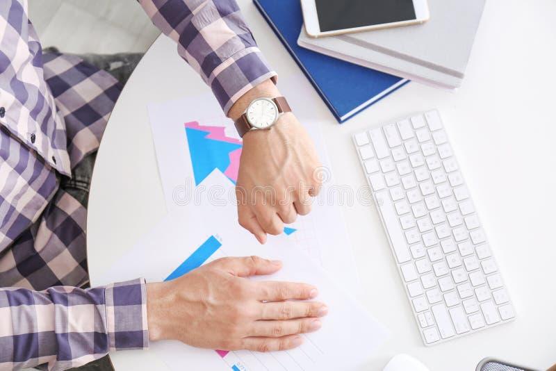 Επιχειρηματίας που ελέγχει το χρόνο στο wristwatch του στον εργασιακό χώρο, τοπ άποψη Χρονική διαχείριση στοκ εικόνα