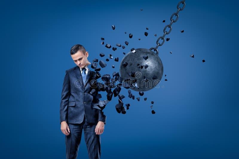 Επιχειρηματίας που εξετάζει κάτω, χέρια τις πλευρές, που καταστρέφονται στα κομμάτια από τη σφαίρα κατεδάφισης στοκ φωτογραφία