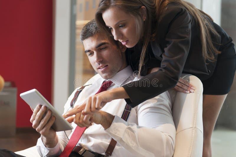 Επιχειρηματίας που εξετάζει πέρα από τον αρσενικό ώμο συναδέλφων που δείχνει την ψηφιακή ταμπλέτα στοκ εικόνες