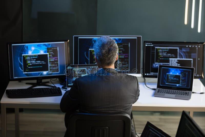 Επιχειρηματίας που εξετάζει τις πολλαπλάσιες οθόνες υπολογιστή στοκ φωτογραφίες με δικαίωμα ελεύθερης χρήσης