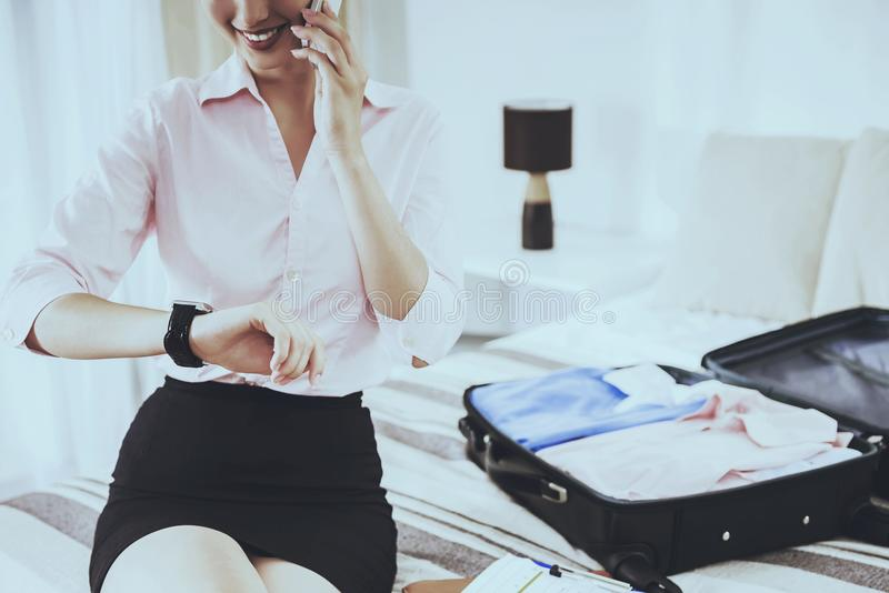 Επιχειρηματίας που εξετάζει το ρολόι και που μιλά στο τηλέφωνο στοκ φωτογραφία