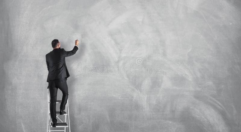 Επιχειρηματίας που επισύρει την προσοχή σε έναν κενό συμπαγή τοίχο, conce ανακοίνωσης στοκ φωτογραφίες με δικαίωμα ελεύθερης χρήσης