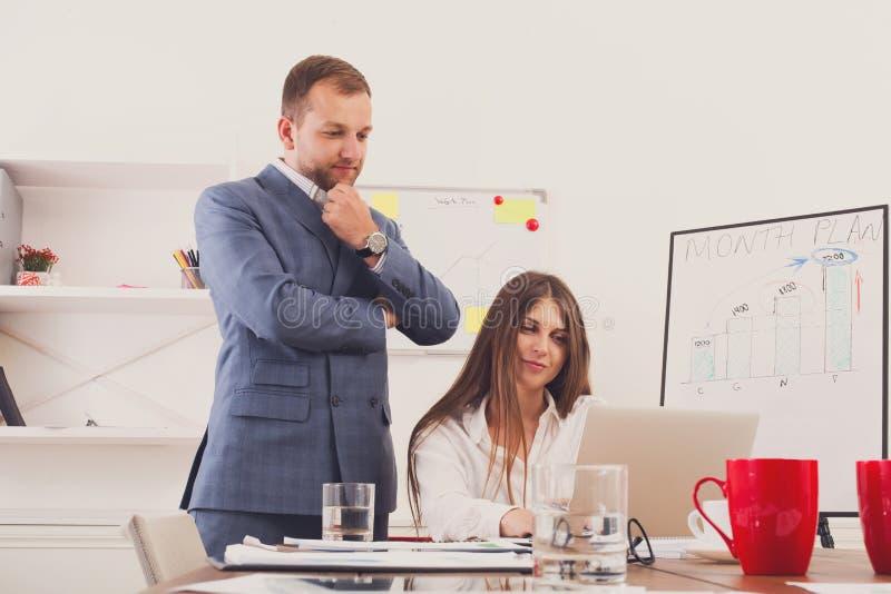 Επιχειρηματίας που εποπτεύει την εργασία του θηλυκού βοηθού του για το φορητό προσωπικό υπολογιστή στοκ εικόνα
