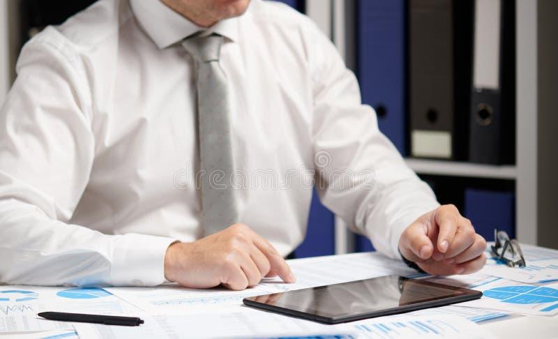 Επιχειρηματίας που εργάζεται με υπολογιστές tablet, υπολογίζει, διαβάζει και γράφει αναφορές Υπάλληλος γραφείου, κλείσιμο πίνακα  στοκ εικόνες