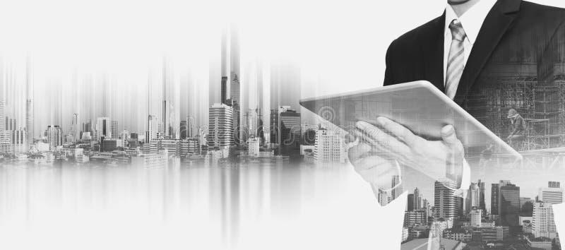 Επιχειρηματίας που εργάζεται στην ψηφιακή ταμπλέτα με τη διπλή πόλη της Μπανγκόκ έκθεσης, έννοιες της ανάπτυξης επιχείρησης ακίνη στοκ εικόνα