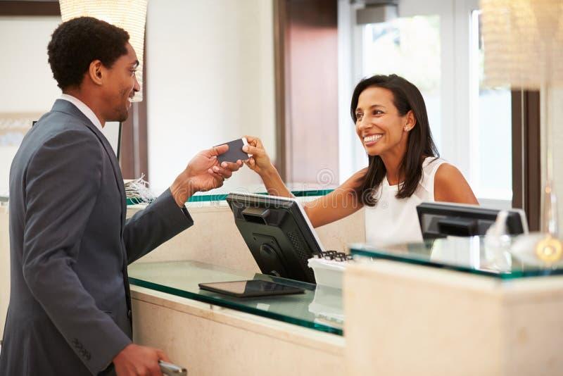 Επιχειρηματίας που ελέγχει μέσα στο μπροστινό γραφείο υποδοχής ξενοδοχείων στοκ εικόνες