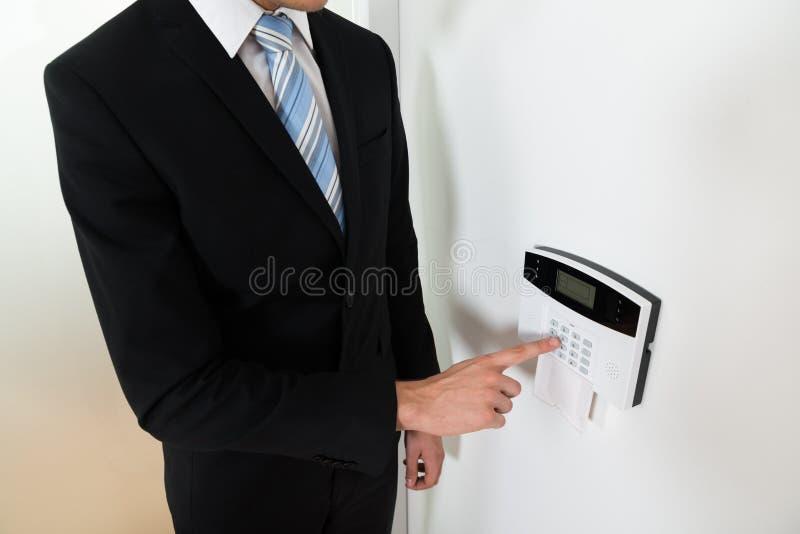 Επιχειρηματίας που θέτει κατ' οίκον το σύστημα συναγερμών ασφάλειας στοκ φωτογραφία με δικαίωμα ελεύθερης χρήσης
