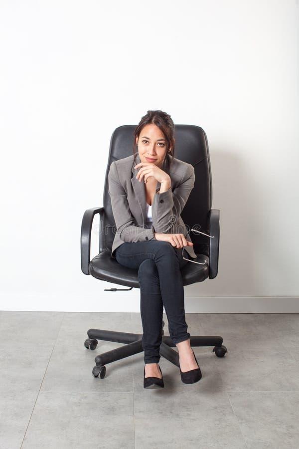 Επιχειρηματίας που θέτει τη συνεδρίαση στην καρέκλα γραφείων για την πρώτη εργασία στοκ εικόνες