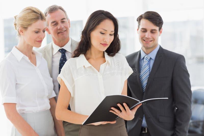 Επιχειρηματίας που διαβάζει ένα έγγραφο με την ομάδα της στοκ εικόνες με δικαίωμα ελεύθερης χρήσης
