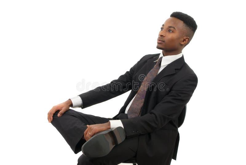 Επιχειρηματίας που κάθεται σε μια καρέκλα που φορά το κοστούμι και το δεσμό στοκ φωτογραφία
