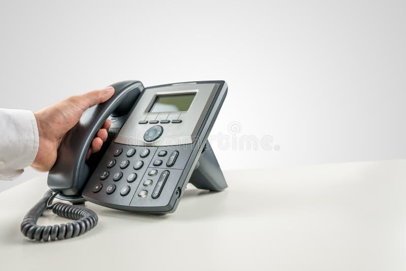 Επιχειρηματίας που κάνει ένα τηλεφώνημα στο τηλέφωνο γραμμών εδάφους στοκ εικόνα
