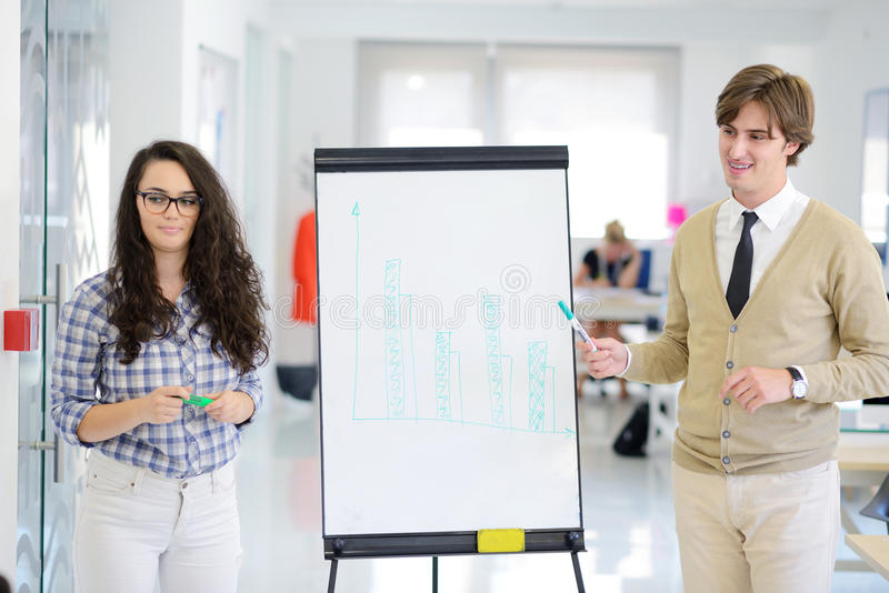 Επιχειρηματίας που κάνει μια παρουσίαση στους συναδέλφους του στην εργασία που στέκεται μπροστά από ένα flipchart στοκ φωτογραφίες με δικαίωμα ελεύθερης χρήσης