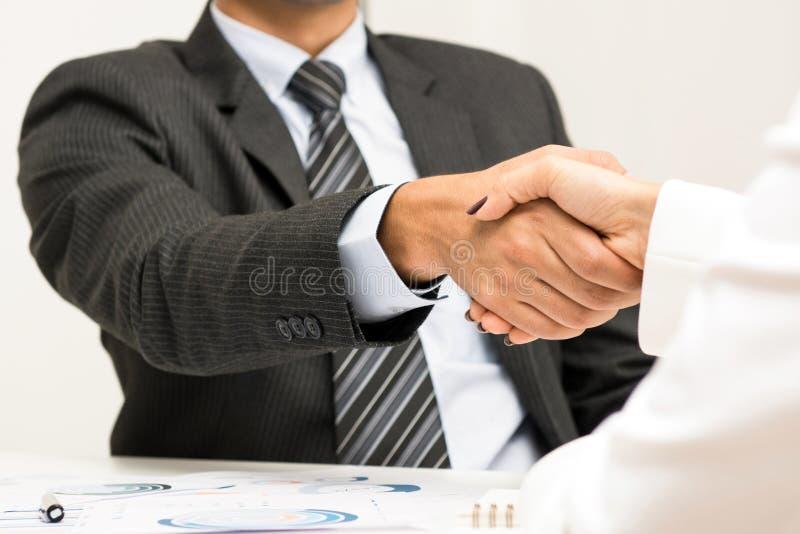 Επιχειρηματίας που κάνει τη χειραψία με μια επιχειρηματία στη συνεδρίαση στοκ φωτογραφία με δικαίωμα ελεύθερης χρήσης