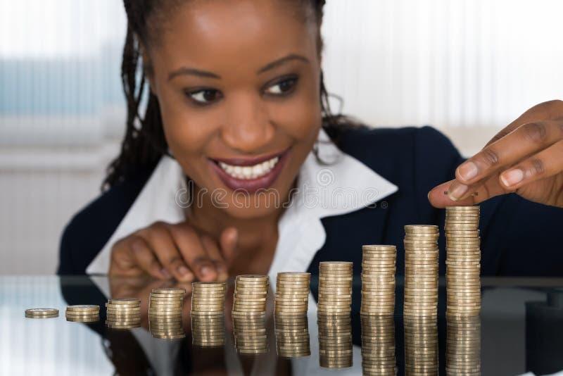 Επιχειρηματίας που κάνει το σωρό των νομισμάτων στοκ φωτογραφία