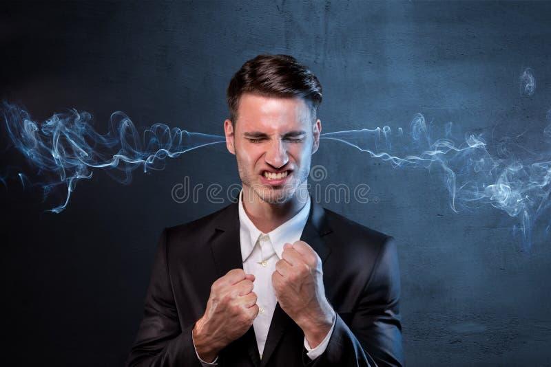 Επιχειρηματίας που καπνίζει με το θυμό στοκ εικόνες