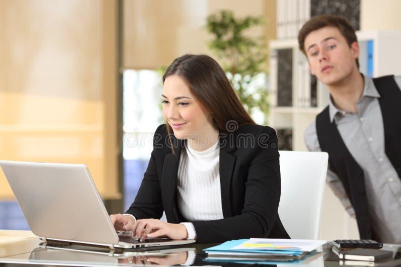 Επιχειρηματίας που κατασκοπεύει το συνάδελφό του στην εργασία στοκ εικόνα