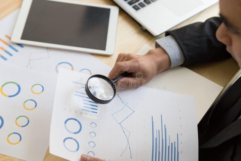Επιχειρηματίας που κοιτάζει μέσω μιας ενίσχυσης - γυαλί στα έγγραφα στοκ εικόνες