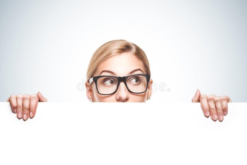 Επιχειρηματίας που κοιτάζει πέρα από την κορυφή του άσπρου σημαδιού στοκ εικόνες