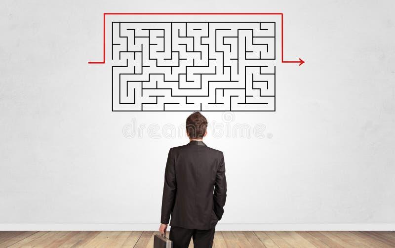 Επιχειρηματίας που κοιτάζει σε έναν λαβύρινθο σε έναν τοίχο στοκ εικόνες