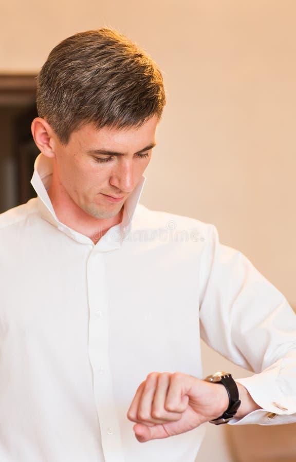 Επιχειρηματίας που κοιτάζει τότε στο Wristwatch του στοκ εικόνα