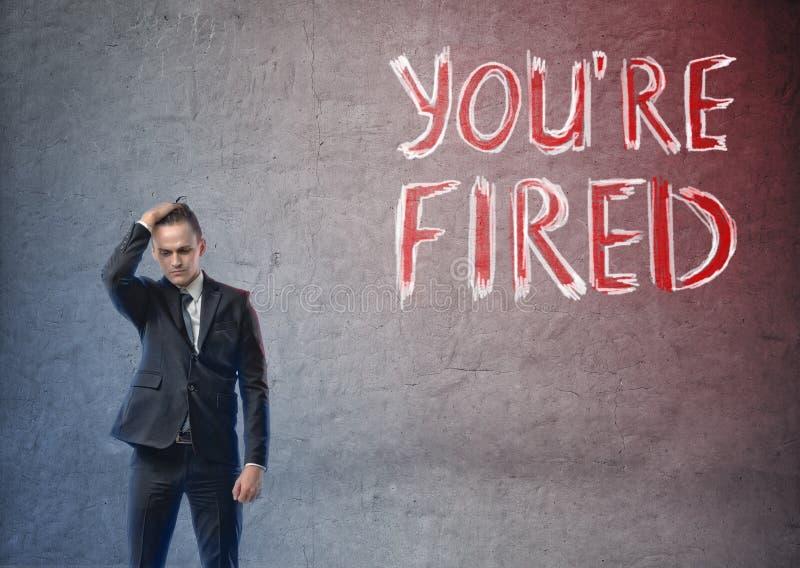 Επιχειρηματίας που κοιτάζουν συντετριμμένα με & x27 you& x27 επαν fired& x27  λέξεις εκτός από τον στοκ εικόνες