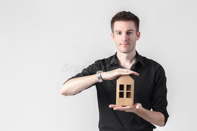 Επιχειρηματίας που κρατά ένα μικρό σπίτι πέρα από το άσπρο υπόβαθρο στοκ εικόνες