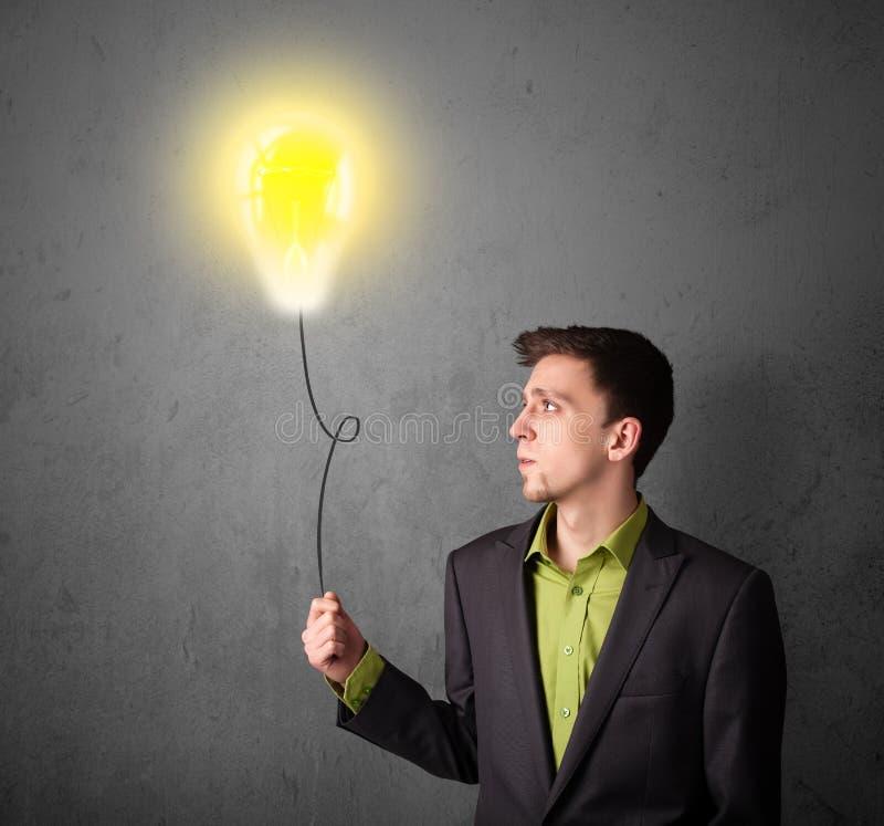 Επιχειρηματίας που κρατά ένα μπαλόνι lightbulb στοκ φωτογραφίες