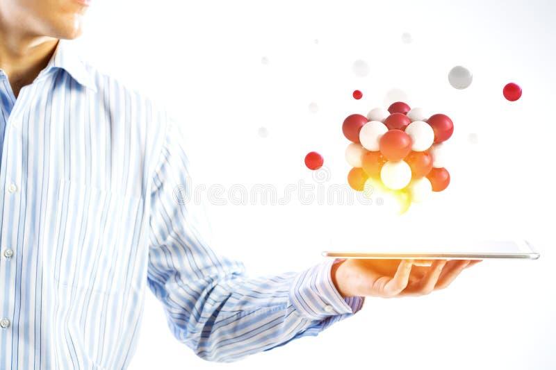 Επιχειρηματίας που κρατά ένα tabalet με μια δέσμη των σφαιρών που ανωτέρω r στοκ φωτογραφία με δικαίωμα ελεύθερης χρήσης