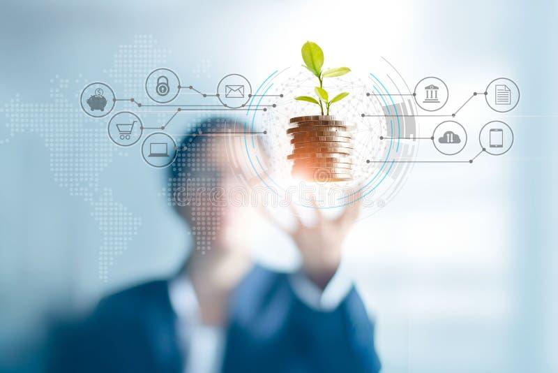 Επιχειρηματίας που κρατά μια ανάπτυξη νεαρών βλαστών δέντρων στα νομίσματα, αφηρημένη επένδυση αύξησης Πελάτης χρηματοδότησης και στοκ εικόνες