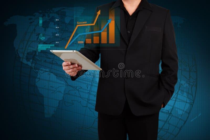 Επιχειρηματίας που κρατά μια ταμπλέτα που παρουσιάζει επιχειρησιακή γραφική παράσταση στο εικονικό s στοκ φωτογραφία με δικαίωμα ελεύθερης χρήσης
