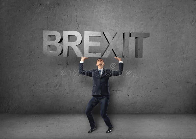 Επιχειρηματίας που κρατά τη βαριά τρισδιάστατη λέξη «brexit» πέρα από το κεφάλι του στοκ φωτογραφίες