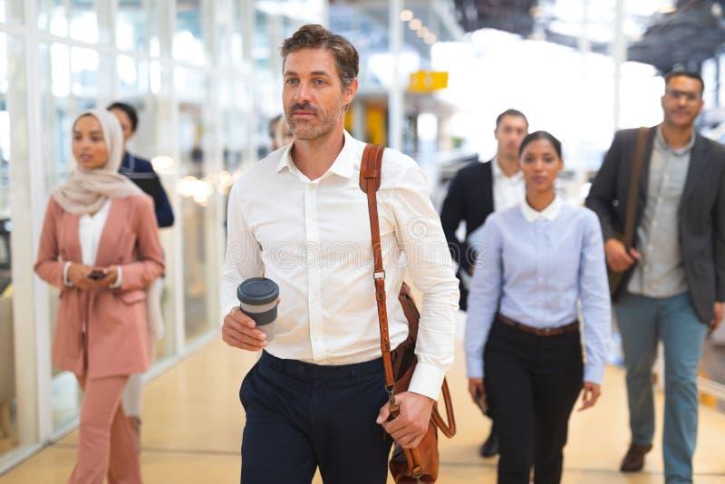 Επιχειρηματίας που κρατά το μίας χρήσης φλυτζάνι καφέ και που περπατά σε ένα σύγχρονο γραφείο στοκ εικόνες με δικαίωμα ελεύθερης χρήσης