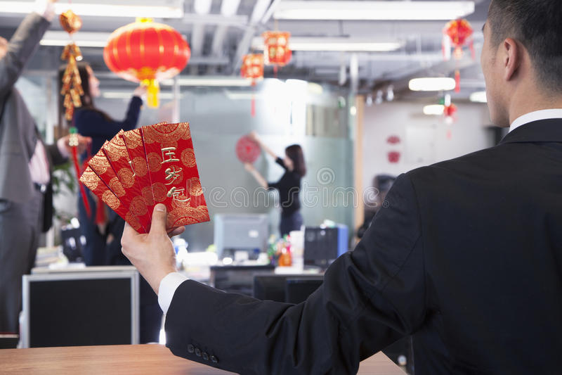 Επιχειρηματίας που κρατούν τους κόκκινους φακέλους και συνάδελφοι που κρεμούν τις διακοσμήσεις για το κινεζικό νέο έτος στοκ εικόνα