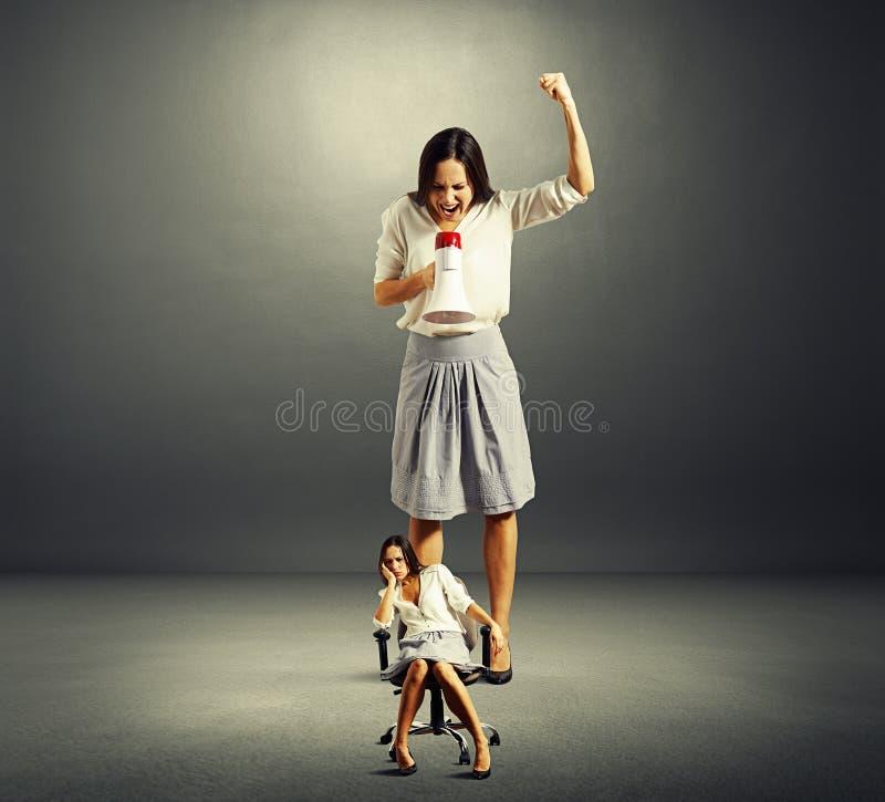 Επιχειρηματίας που κραυγάζει στην οκνηρή γυναίκα στοκ φωτογραφίες
