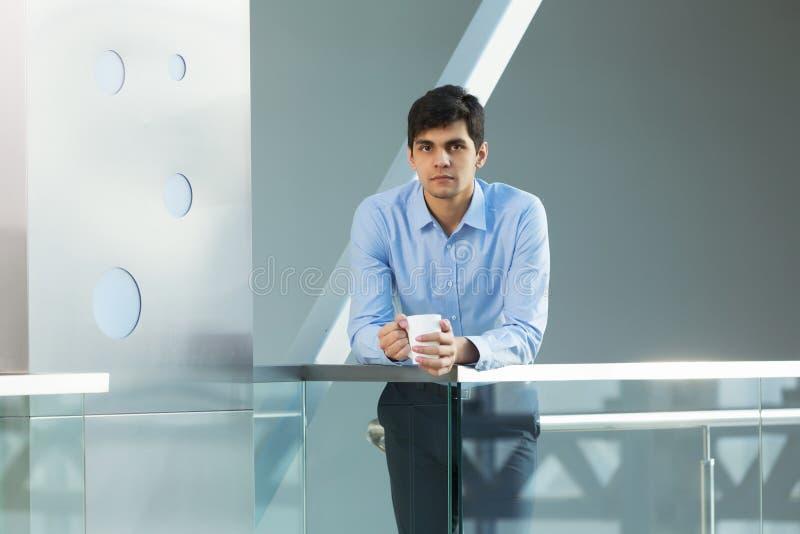 Επιχειρηματίας που κλίνει στα κιγκλιδώματα μπαλκονιών στοκ φωτογραφία