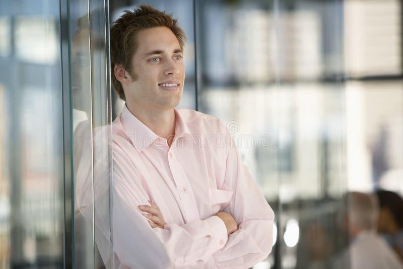 Επιχειρηματίας που κλίνει στην πόρτα γυαλιού γραφείων στοκ φωτογραφία με δικαίωμα ελεύθερης χρήσης