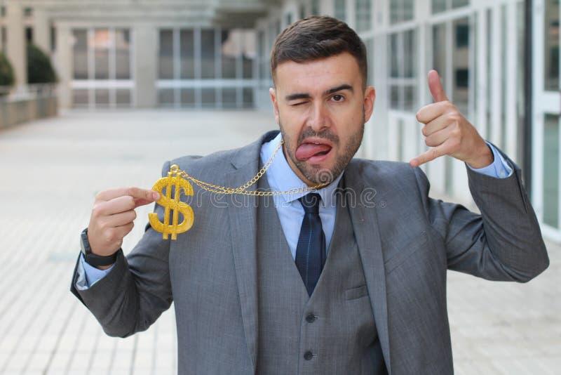 Επιχειρηματίας που λικνίζει το χρυσό περιδέραιο με το σημάδι δολαρίων στοκ φωτογραφίες