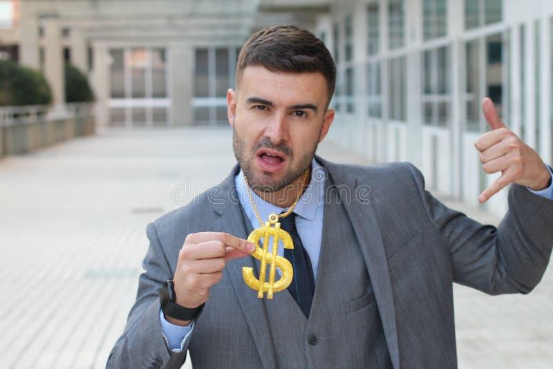 Επιχειρηματίας που λικνίζει το χρυσό περιδέραιο με το σημάδι δολαρίων στοκ εικόνα