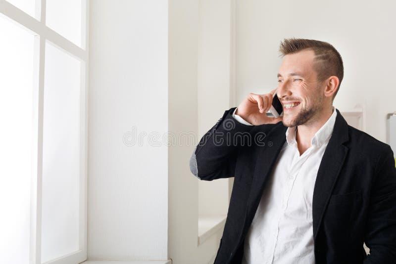 Επιχειρηματίας που μιλά με τηλέφωνο, που στέκεται κοντά στο παράθυρο στοκ φωτογραφίες με δικαίωμα ελεύθερης χρήσης