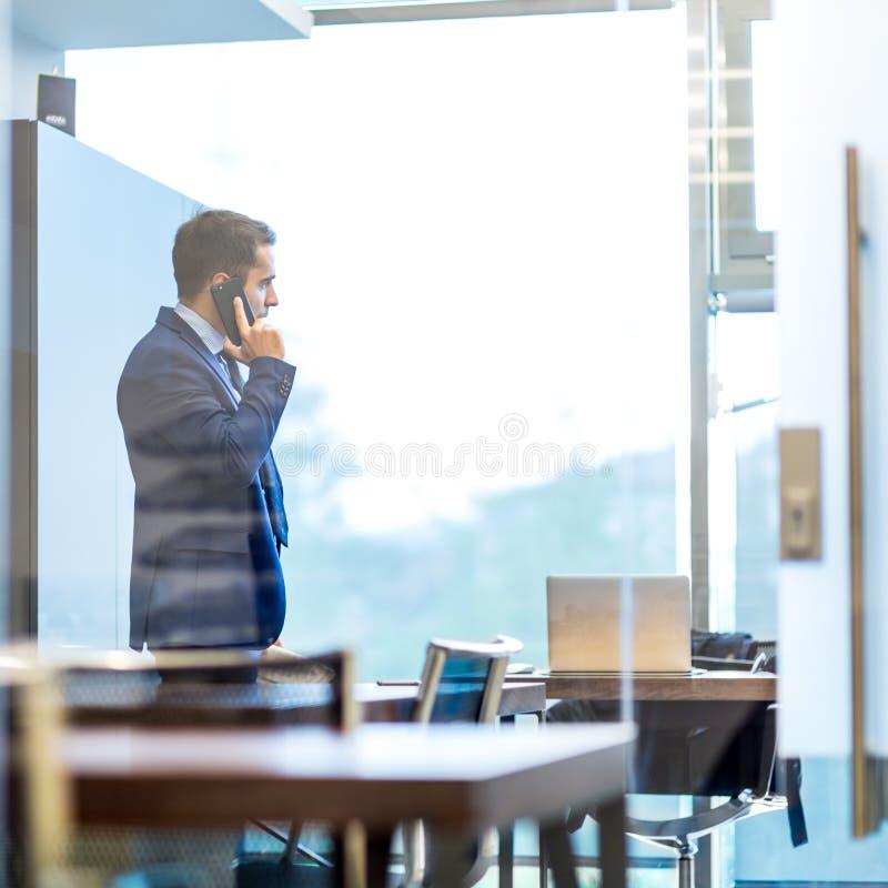 Επιχειρηματίας που μιλά σε ένα κινητό τηλέφωνο κοιτάζοντας μέσω του παραθύρου στοκ εικόνες