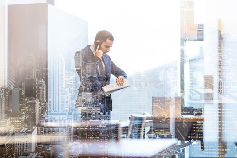 Επιχειρηματίας που μιλά στο κινητό τηλέφωνο εξετάζοντας το wristwatch στοκ εικόνα