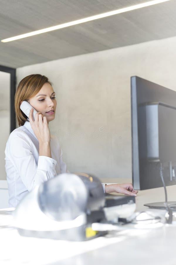 Επιχειρηματίας που μιλά στο τηλέφωνο καθμένος στο γραφείο υπολογιστών στην αρχή στοκ φωτογραφίες