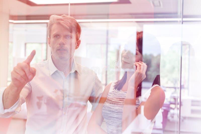 Επιχειρηματίας που μιλά στο smartphone στεμένος με το συνάδελφο στο γραφείο στοκ εικόνα