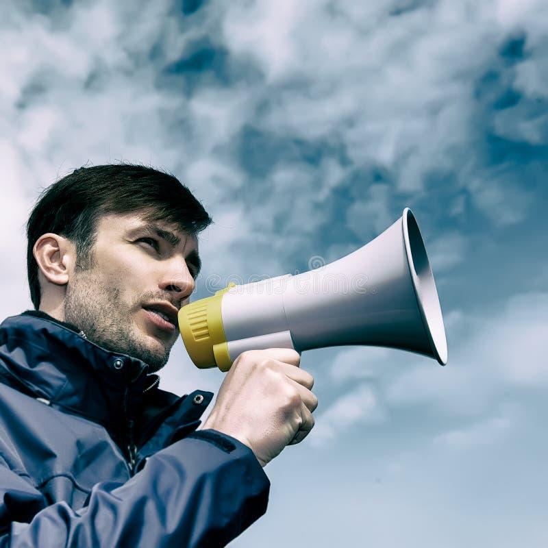 Επιχειρηματίας που μιλά megaphone ενάντια στον ουρανό στοκ φωτογραφία