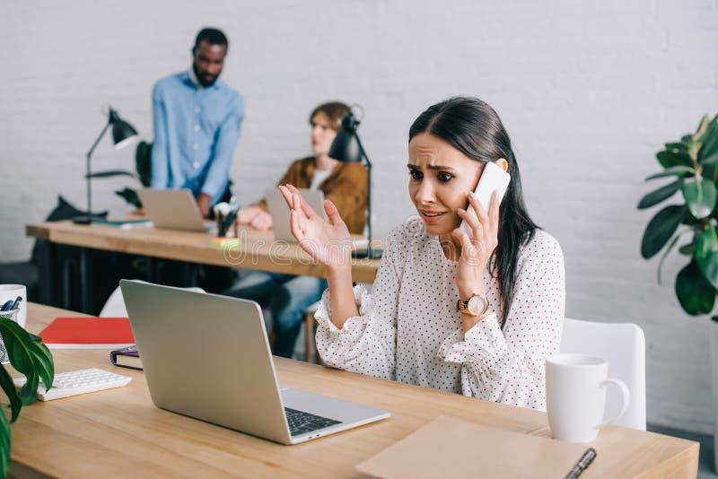 επιχειρηματίας που μιλούν στο smartphone και συνάδελφοι που εργάζονται πίσω σε σύγχρονο στοκ εικόνα με δικαίωμα ελεύθερης χρήσης