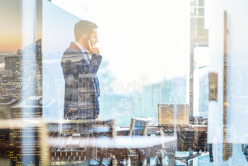 Επιχειρηματίας που μιλά σε ένα κινητό τηλέφωνο κοιτάζοντας μέσω του παραθύρου στη Νέα Υόρκη στοκ εικόνες