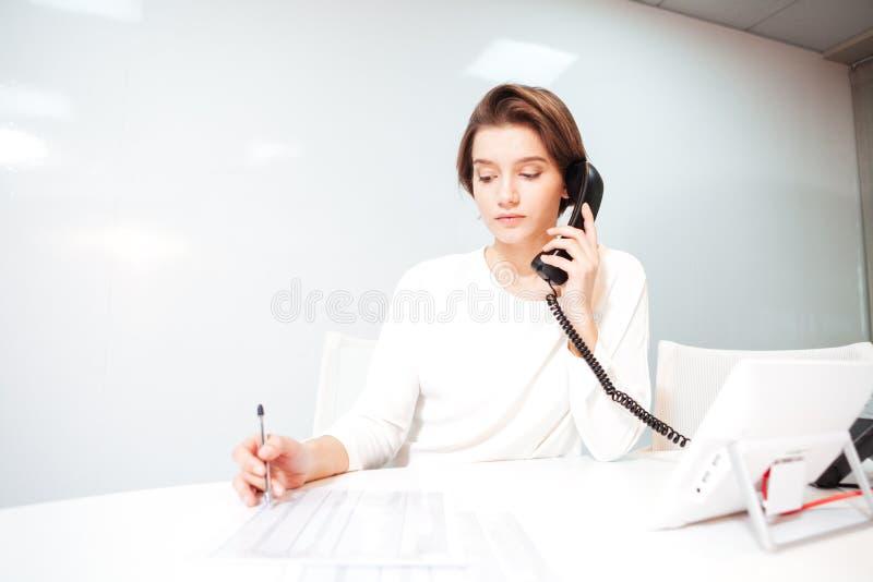 Επιχειρηματίας που μιλά στο τηλέφωνο στην αρχή στοκ εικόνες