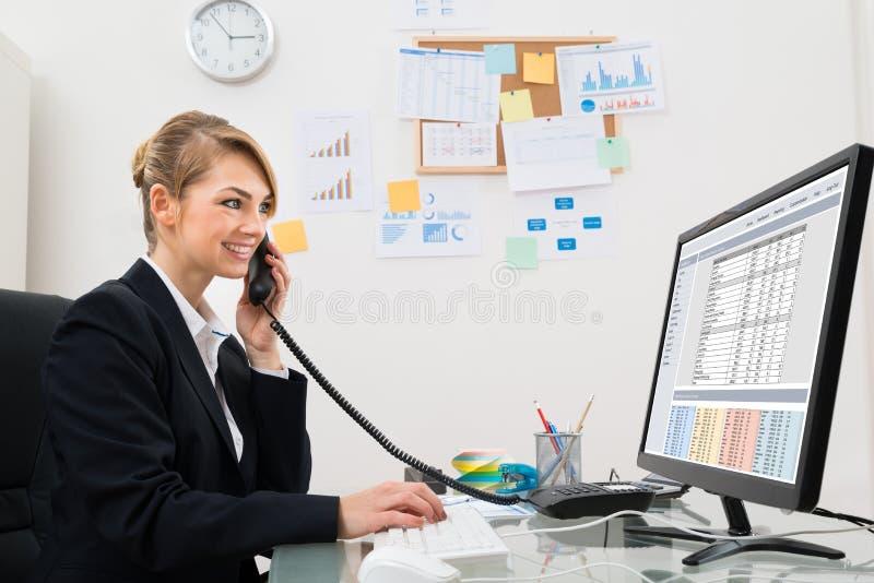 Επιχειρηματίας που μιλά στο τηλέφωνο στο γραφείο στοκ φωτογραφία με δικαίωμα ελεύθερης χρήσης